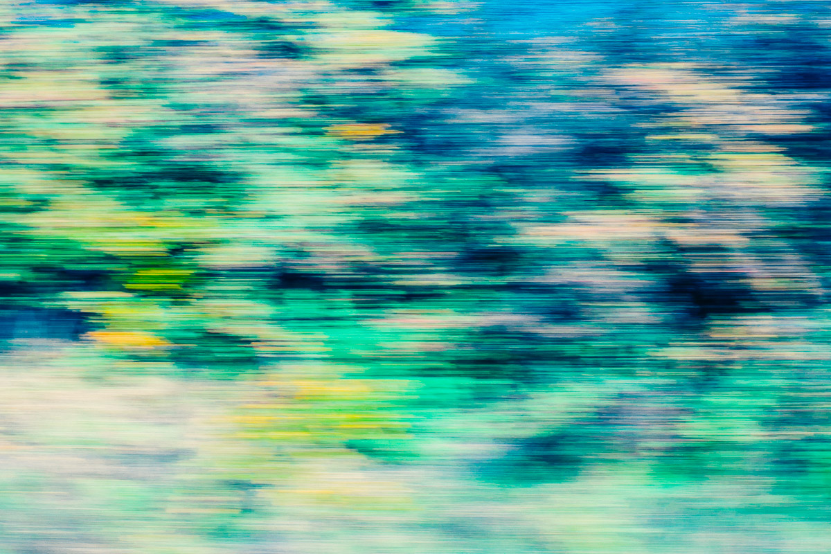 Abstraktes buntes Bild einer Landschaft aufgenommen in Bewegung, mit Farbakzenten in blau, grün, türkis und gelb