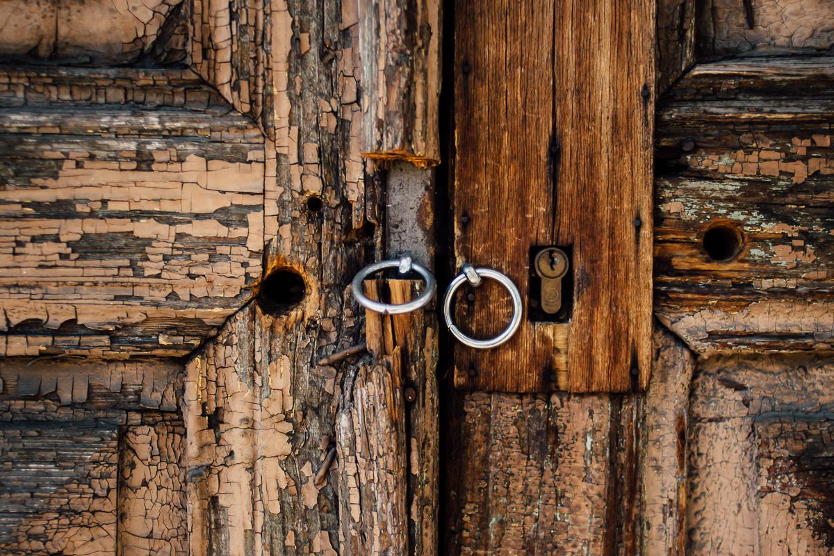 Verwitterte alte Holztür mit Metallringen
