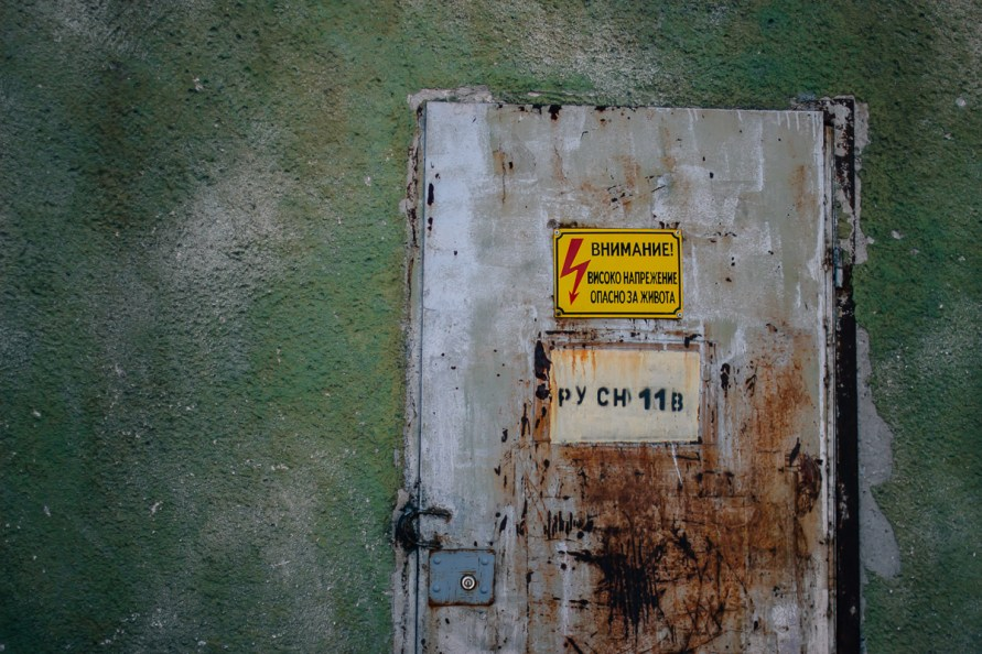 Old rusty door with signs in green wall