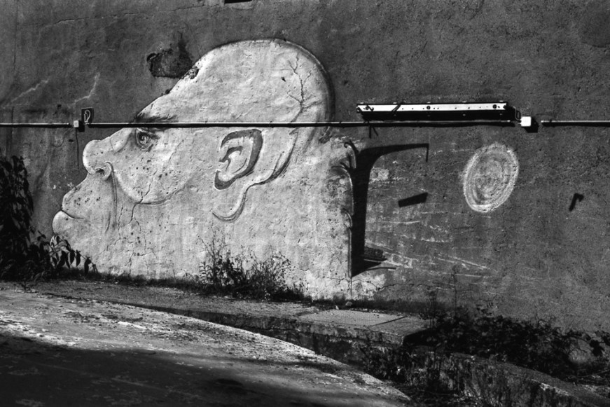 Old wall with graffiti painting showing a large bald head