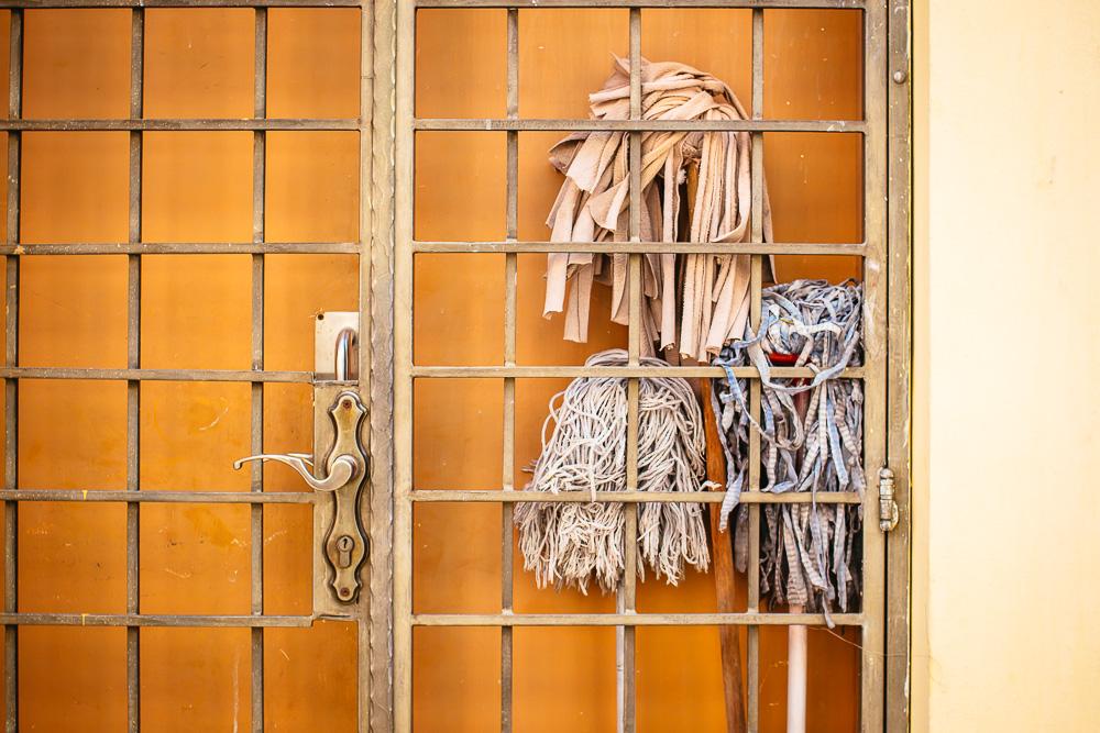 three mops behind metal gate with orange background