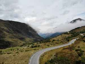 scenic landscape of road in mountainous valley against misty sky