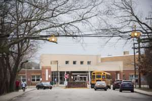 a yellow school bus on a city street: The main entrance to Brentwood High, one of New York's largest secondary schools.