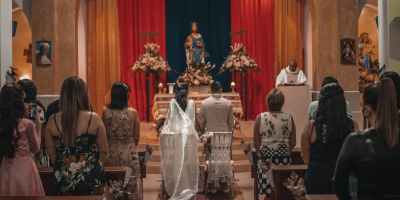 unrecognizable newlyweds and guests standing in church hall