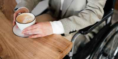 crop disabled woman with cup of coffee in cafeteria