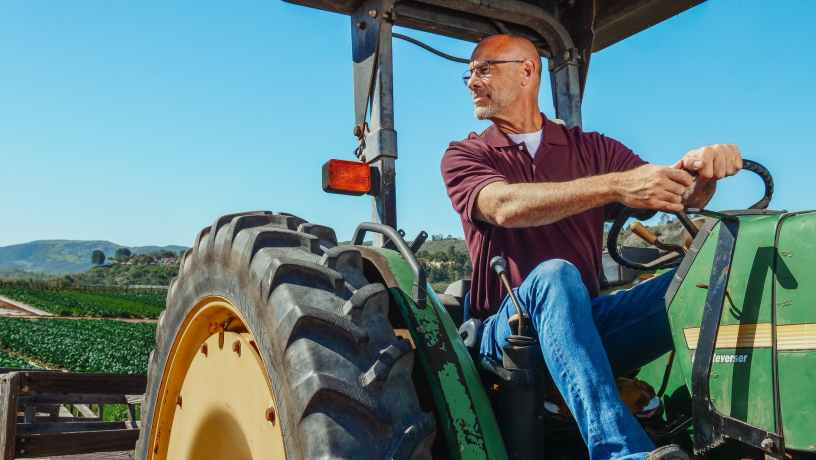 man in brown and white stripe polo shirt and blue denim jeans sitting on green tractor