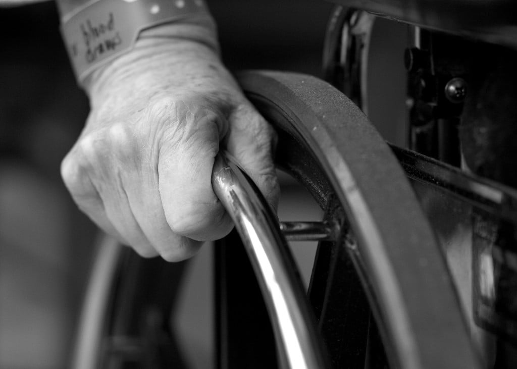 Hand of an elderly person, on the wheel of a wheelchair