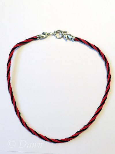Red and black Kuminimo cord topped off with horse-head terminals