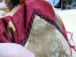 Embellishing the black trim with red embroidery