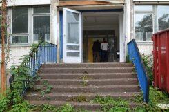 """Der DDR-Schulbau aus den 1970ern lag seit zehn Jahren brach. Löwenzahn wächst aus den Eingangsstufen zur 46. Oberschule an der Andreas-Schubert-Straße. Aber die Statik stimmt nach wie vor. Alles andere muss erneuert werden. """"Eine Generalsanierung"""", sagt Projektleiterin Raina Kurz vom Hochbauamt. Sie nennt die energetische Sanierung und die Verschönerung der Innenhöfe. """"In einem führt eine große Treppenanlage in den Speiseraum im Untergeschoss"""", erklärt die Projektleiterin. """"Der andere wird begrünt und mit Bänken ausgestattet."""" Hier geht es im August richtig los, die Fertigstellung ist für Jahresbeginn 2017 geplant. Die Sanierung des Hauses, welches nach der Wende als Außenstelle des Beruflichen Schulzentrums für Gesundheit und Soziales genutzt worden war, kostet 9,3 Millionen Euro – auch diese sind Eigenmittel der Stadt. Foto: Thessa Wolf"""