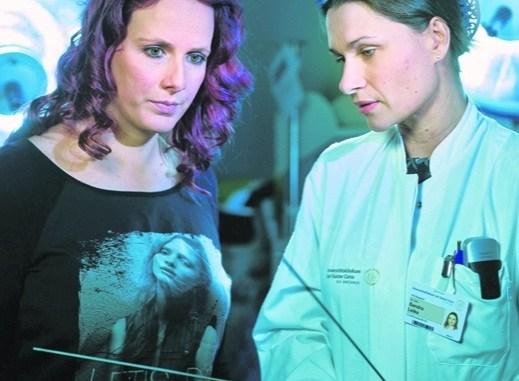 Patientin Maria Streubel hat einen makellosen Hals – ohne Narbe. Sandra Leike von der Uniklinik Dresden zeigt die Millimeter dünnen Instrumente, die alternativ eingeführt werden. Foto: R. Bonß
