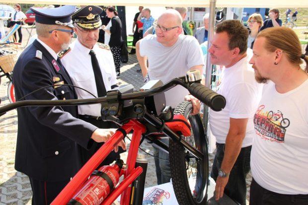 Beim Rundgang wurde auch der Präsident des Deutschen Feuerwehrverbands Hartmut Ziebs (2. v.l.) auf das Bike aufmerksam.