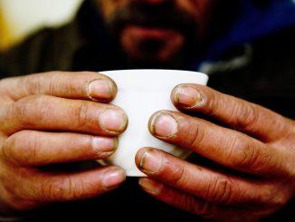 Ein obdachloser Mann hält eine Tasse. Foto: Sebastian Kahnert/Archiv