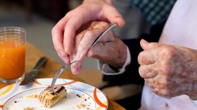 Ein Mann hilft einer alte Frau beim Einnehmen einer Mahlzeit. Foto: Friso Gentsch/Archiv