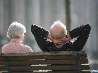 Ein Rentnerpaar sitzt auf einer Bank und sonnt sich. Foto: Stephan Scheuer/Archiv