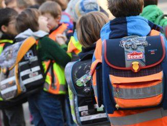Schüler tragen ihre Schulranzen. Foto: Arne Dedert/Archiv