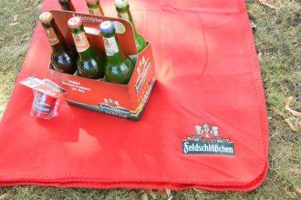 """DAWO! verlost 6 """"Feldi-Pakete"""" zur Kaisermania 2018 bestehend aus 2 Flaschenöffner, 6er Pack Feldschlösschen und eine bestickte Picknickdecke. (Foto: Juliane Zönnchen)"""