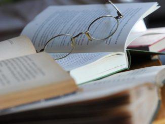 Eine Lesebrille liegt auf einem Bücherstapel. Foto: Jens Kalaene/Archiv