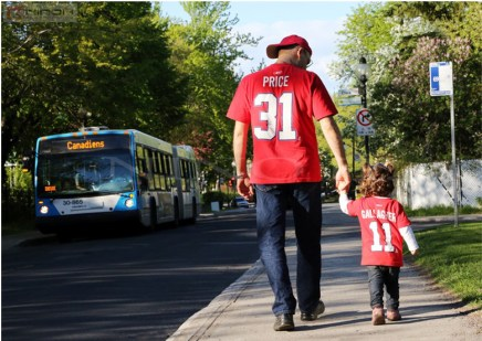 An STM bus displaying its support for the team passes a father and daughter wearing their Habs t-shirts.(Photo-Nino H).