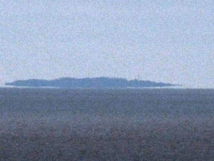 Hesselø - fyret anes, men øen er ligesom ved at lette fra havets overflade