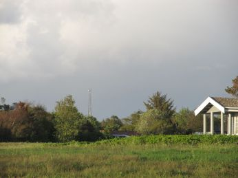 Vejby Kystradar ses i baggrunden - et andet dejligt søjlesommerhus til højre