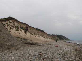 Det smukke okkerfarvede sand i den styrtede skråning ligesom skinner i gråvejret