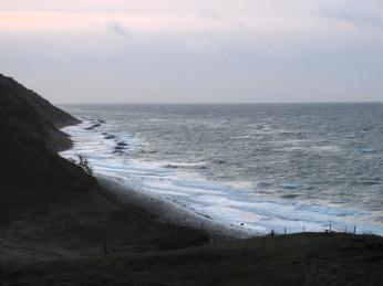 Man ser kystbeskyttelsens stensætninger midt i brændingen