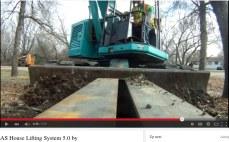 En gravemaskine skubber stålbjælke ind under huset