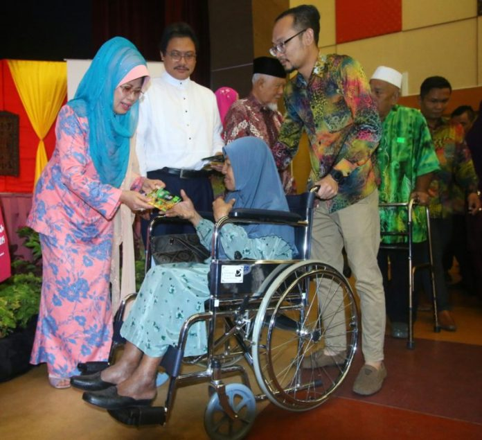 Fatimah presenting the RM100 aid to a recipient.