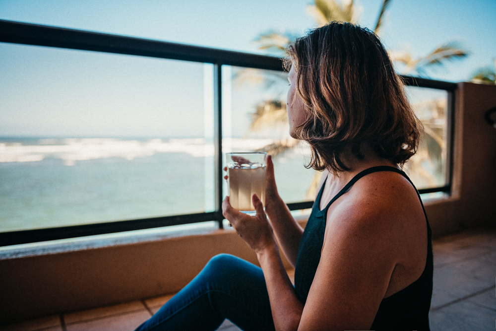 healthy woman drinking detox drink staring serenely at ocean with beautiful background