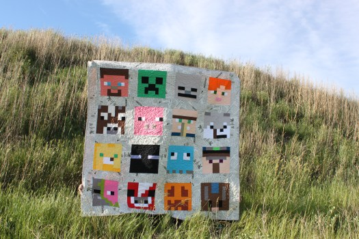 Minecraft quilt with sixteen Minecraft character blocks.