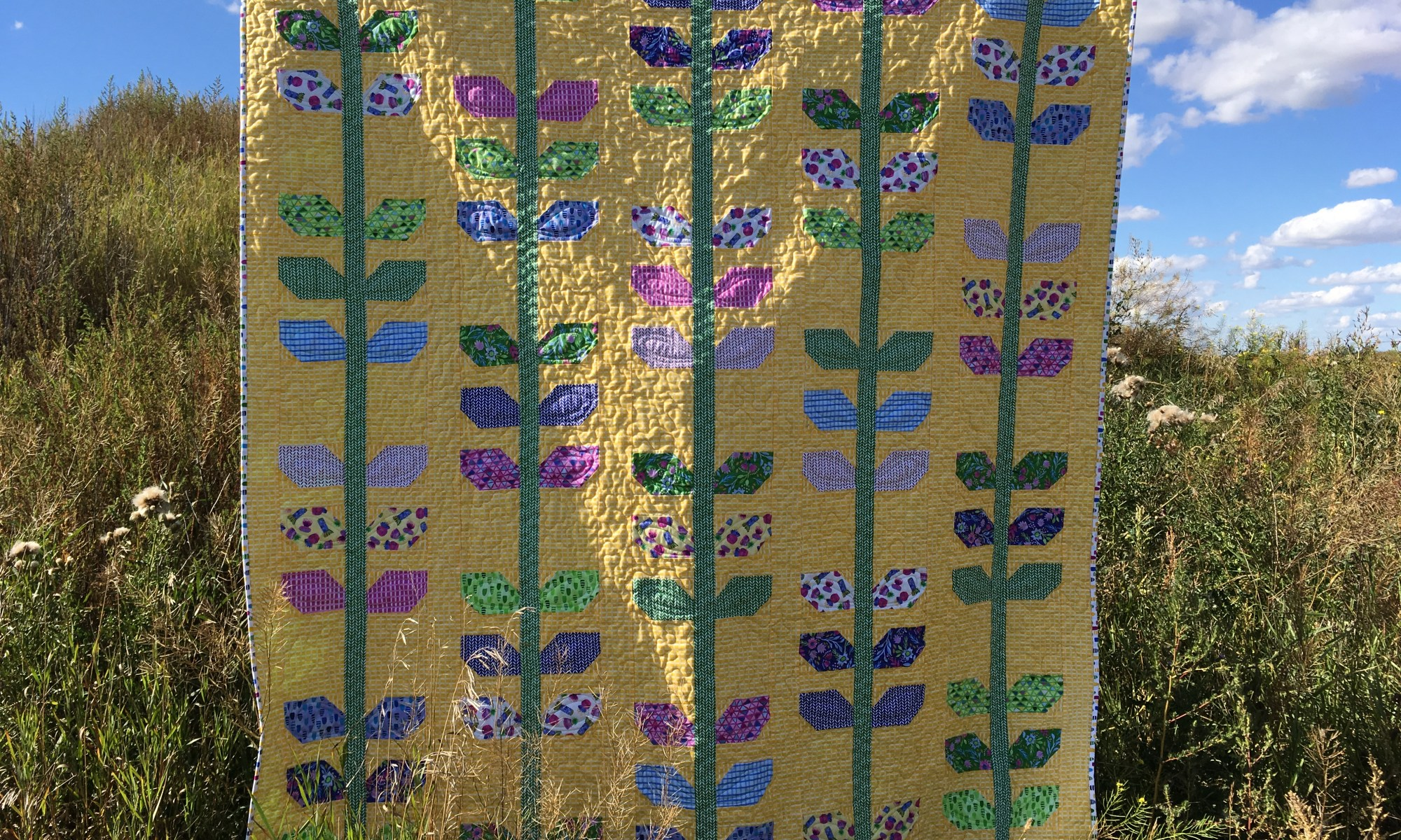 Horizontal photo of the Garden Vines / Morning Glory quilt.