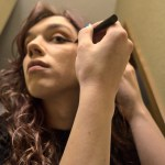 """8 a.m. —Allison comments as she applies eyeliner on Tuesday, April 14, 2020, """"This keeps me sane some days. It's all about maintaining that bit of normalcy. If it takes flashy makeup to keep me from going stir-crazy, I'll keep drawing wings."""""""