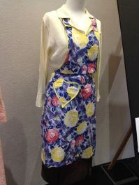 Jean - Cream rayon blouse, brown-multicoloured skirt with belt & blue, red, yellow floral apron with bib