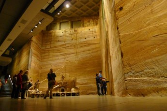 Visitors are drawn in wonder to the sandstone wall which, not being an art exhibit, can be touched (gently)