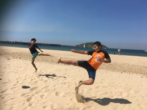 two boys doing karate kick at the beach