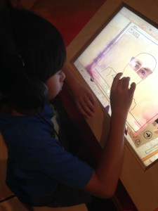 boy creating a face on a touch screen