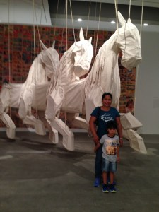 mother and son with giant white horses behind them
