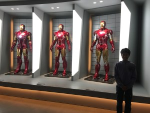 a boy with three Iron Man suits