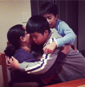 three boys hugging their mother