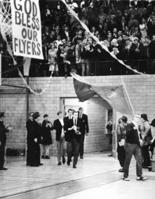 Image shows the University of Dayton celebrating their NIT Championship victory