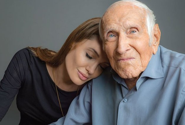 """This undated photo provided by Universal Pictures, Angelina Jolie is photographed with Louis Zamperini. Zamperini, a U.S. Olympic distance runner and World War II veteran who survived 47 days on a raft in the Pacific after his bomber crashed, then endured two years in Japanese prison camps, died Wednesday, July 2, 2014, according to Universal Pictures studio spokesman Michael Moses. He was 97.  Jolie is directing the Universal movie, """"Unbroken,"""" about the life of Zamperini. (AP Photo/Universal Pictures)"""