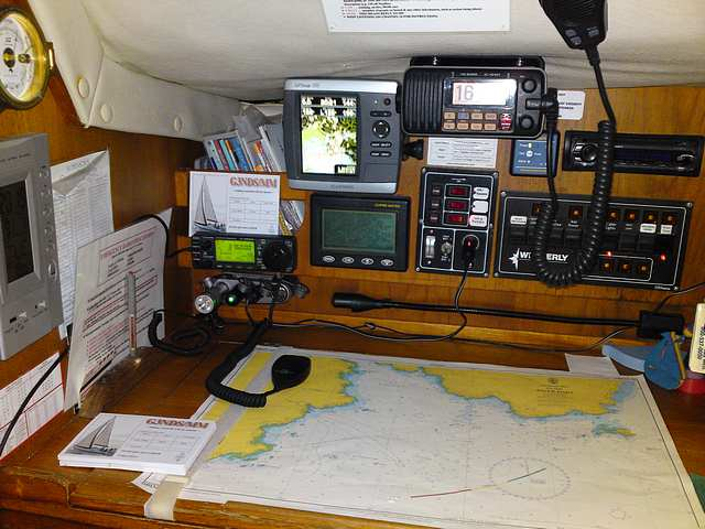 Navigation Table on Christine Marie.  Amateur Radio SSB receiver LHS, Marine VHF top.  GPS and Navtext to left of VHF.