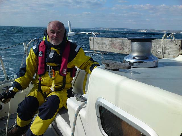 Brian at the helm crossing Weymouth Bay, Jurassic Coast in background.