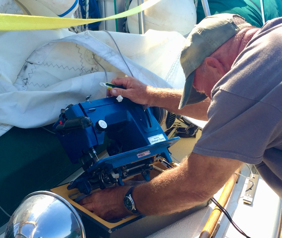 Captain Dan sews the mainsail on deck while underway.