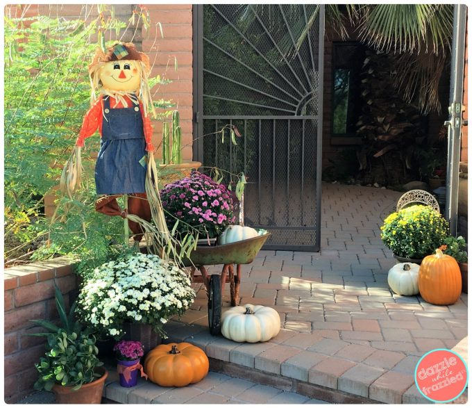 Decorate front porch for autumn with mums, scarecrows and vintage polyurethane pumpkins.