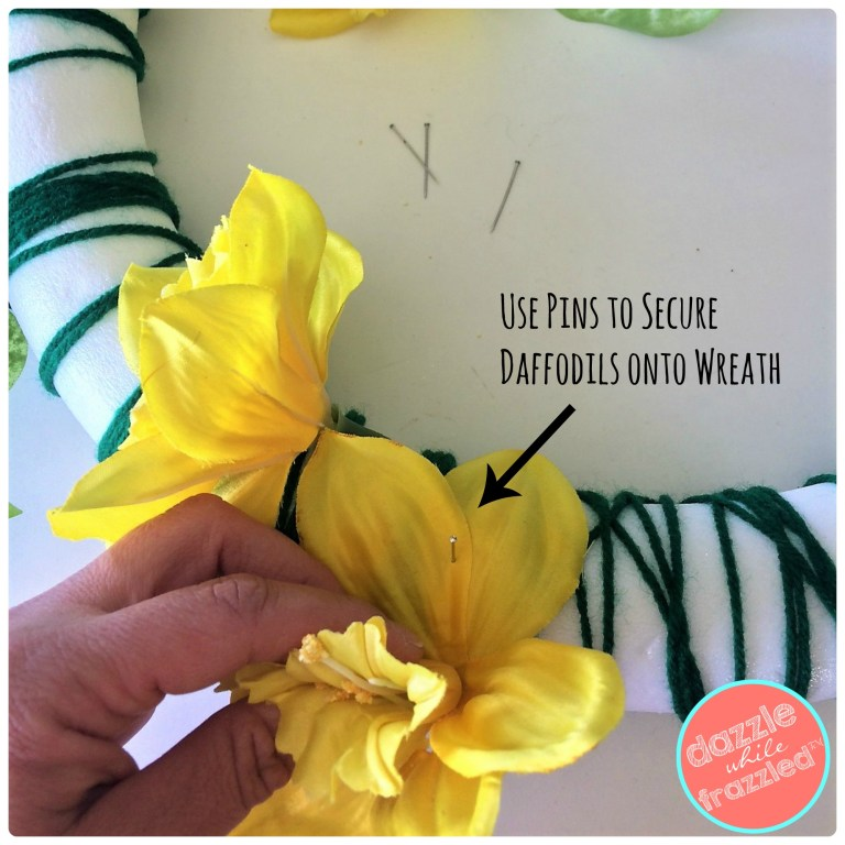 Use straight pins to secure spring daffodils onto foam wreath covered with green yarn.