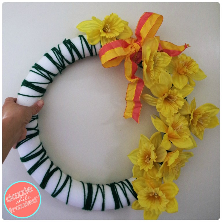 Colorful yellow daffodil spring wreath with green yarn wrapped around a foam wreath.