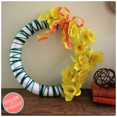 Make a pretty daffodil front door wreath for spring home decor using faux daffodil flowers and green yarn wrapped around a foam wreath.
