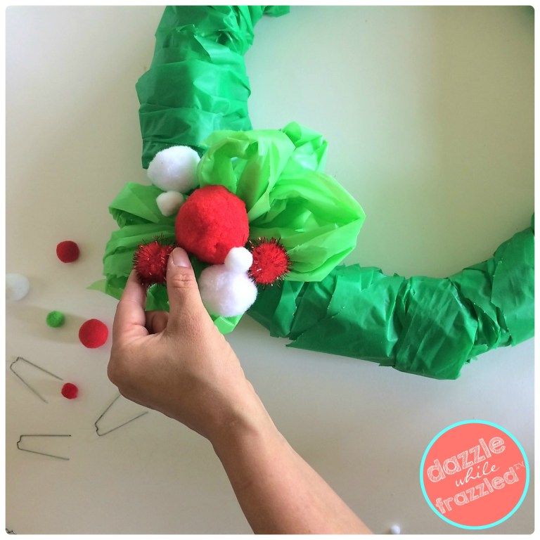 Hot glue red, green and white Christmas pom poms to make a cheap $2 DIY Christmas poinsettia themed door wreath.